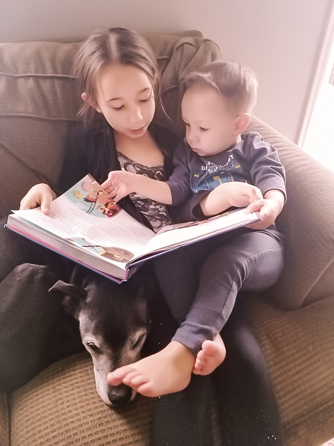 Child reading to toddler